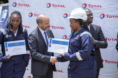 Mr. Pierre Jessua, Total E&P Uganda General Manager (C) hands over a certificate to Dez Liz Habwahangirwe one of the graduating students from the Total E&P Uganda Welders training program. Looking on is Samuel Araali Kisembo, Resident District Officer hoima looks on (R)
